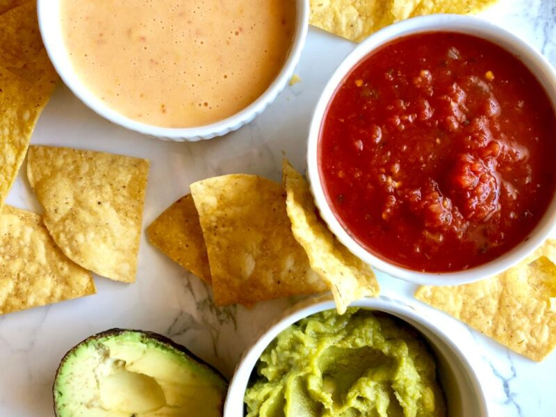 chips, salsa, guacamole and queso on a counter