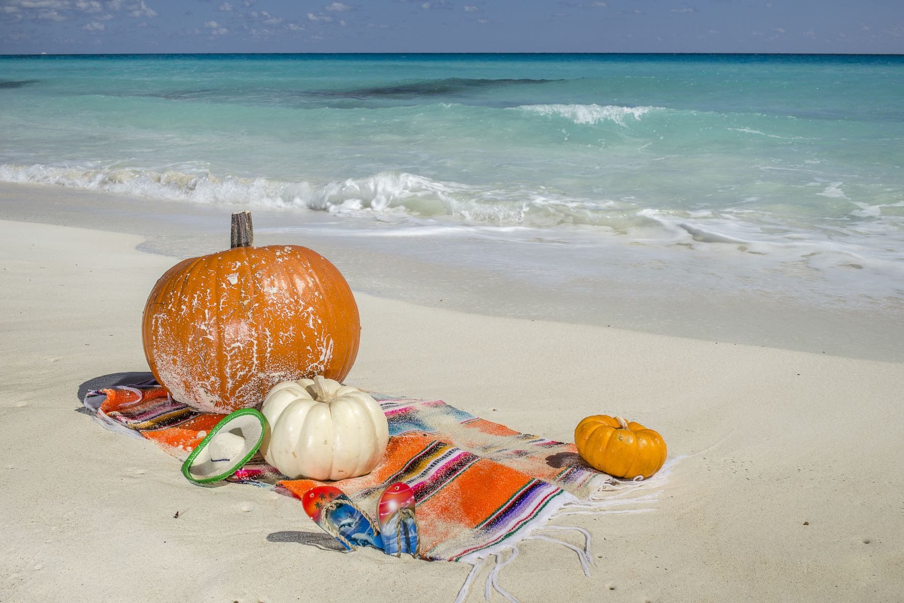 pumpkins on a towel on the beach